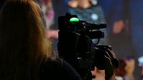 女孩录影操作员 表现的电视录象制作在阶段的 对大屏幕播放录影 居住在电视 影视素材