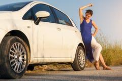 女孩得到小便在他残破的汽车 免版税图库摄影