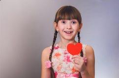女孩微笑和举行手中心脏 免版税库存照片