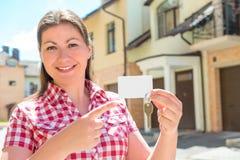 女孩微笑和点对钥匙的公寓 库存图片