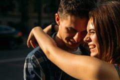 女孩微笑并且拥抱人` s脖子用两只手 人微笑和谨慎地降低他的头 的女孩 库存照片