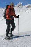 女孩微笑的雪靴行程 库存图片