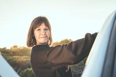 女孩微笑,坚持车门 旅行和自由的概念 免版税库存图片