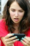 女孩怀疑地在移动电话或移动电话文本 免版税图库摄影