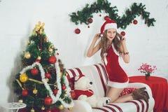 女孩性感的圣诞老人 库存照片