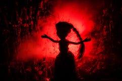 女孩恐怖剪影在表面无光泽的玻璃血迹后的 模糊的手和身体形象抽象 与火的背景 库存图片