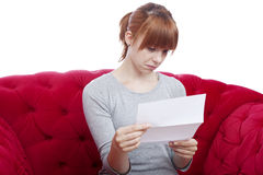 女孩恶化在红色沙发的新闻 免版税图库摄影