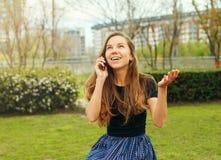 女孩情感地谈话在电话 免版税库存图片