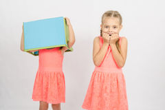 女孩惊吓了佩带在他的头的姐妹一个箱子 免版税库存照片