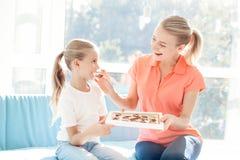 女孩惊奇为她的母亲做准备 女儿给了母亲一箱巧克力 库存图片