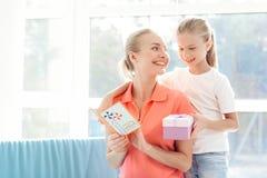 女孩惊奇为她的母亲做准备 小女孩一件礼物为妈妈做准备 免版税库存照片