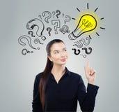 女孩想法 有黄色电灯泡的聪明女人学生 突发的灵感、问题和解答概念 免版税库存照片