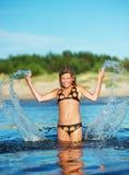 女孩愉快做飞溅水 免版税图库摄影