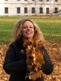 女孩愉快叶子槭树投掷 免版税库存图片