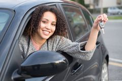 女孩愉快在购买一辆新的汽车以后 库存图片