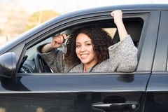 女孩愉快在购买一辆新的汽车以后 免版税图库摄影