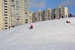 女孩愉快地滑在雪管的雪小山下 库存照片