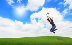 女孩愉快的上涨填充个人计算机显示接触 免版税图库摄影