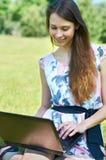 女孩愉快的公园个人计算机 图库摄影