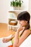 女孩愉快的家庭膝上型计算机放松少&# 免版税库存图片