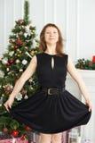 女孩愉快的年轻人 黑色礼服 圣诞节内部 圣诞节我的投资组合结构树向量版本 库存照片