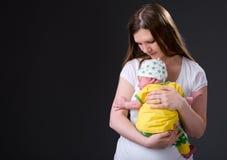 女孩愉快的母亲新出生的年轻人 免版税库存图片