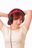 女孩愉快的耳机听音乐年轻人 免版税图库摄影