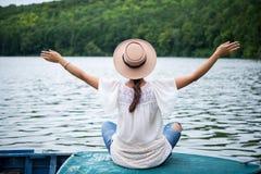 女孩感到自由在湖的一条小船 库存图片