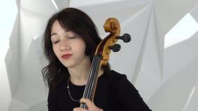 女孩戏剧弹小提琴的大提琴两女孩在白色演播室 股票视频