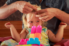 女孩戏剧玩具建设者父亲掠过她的头发特写镜头 免版税库存图片