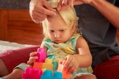 女孩戏剧玩具建设者父亲掠过她的头发特写镜头 图库摄影