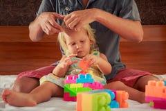 女孩戏剧玩具建设者父亲掠过她的头发 免版税库存图片
