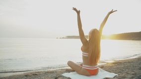 女孩戏剧的剪影与她的头发的在慢动作的日落 晚上凝思,妇女实践在海滨的瑜伽 影视素材