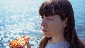 女孩截去比萨饼并且嚼它在海背景  股票视频