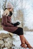 女孩户外阅读书在冬天 免版税库存照片