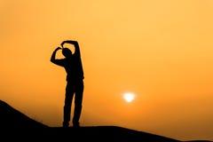 女孩手做的心脏剪影在日落 免版税库存照片