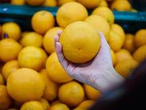女孩手对负橙色为购物在商店 免版税库存图片