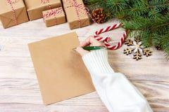 女孩手文字在工艺纸的圣诞节信件与在木背景的装饰 免版税库存照片