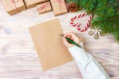 女孩手文字在工艺纸的圣诞节信件与在木背景的装饰 免版税库存图片