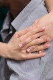 女孩手特写镜头拥抱男朋友肩膀的 免版税库存照片