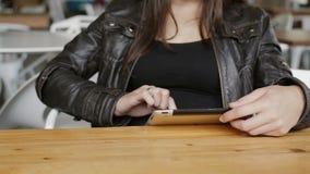 女孩手的特写镜头在现代咖啡馆使用一朵片剂海浪坐的互联网 4K 免版税库存图片
