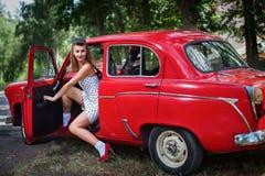 女孩打开汽车的门 免版税库存照片