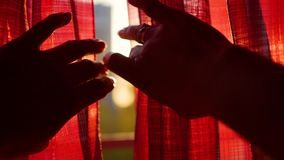 女孩打开红色帷幕和使用用他的手通过太阳` s光芒 手特写镜头 股票录像