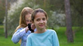 女孩打褶她的女朋友辫子  友谊关系的概念 股票视频