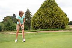 女孩打高尔夫球少年 免版税库存照片