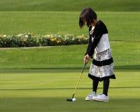 女孩打高尔夫球 库存图片