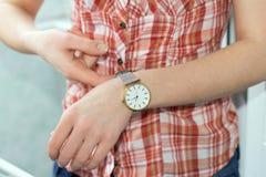 女孩扣紧手表 免版税库存照片