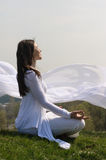 女孩执行在小山的瑜伽反对蓝天 免版税图库摄影