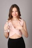 女孩把她的手指指向瓶水 关闭 灰色背景 免版税库存照片