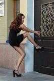 女孩投入了她的脚门并且想要开放它 库存图片